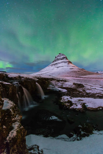 Aurora Borealis or northern light above kirkjufell mountain in iceland Aurora Borealis Iceland Kirkjufell Astronomy Aurora Polaris Beauty In Nature Cold Temperature Environment Green Color Idyllic Landscape Long Exposure Mountain Nature Night No People Non-urban Scene Nothernlights Scenics - Nature Sky Space Star - Space Tranquil Scene Tranquility