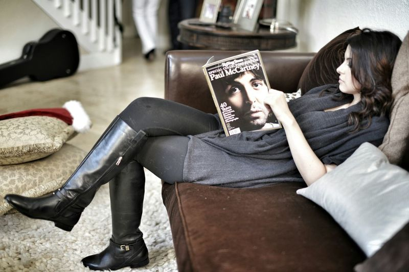 Woman reading magazine while relaxing on sofa at home