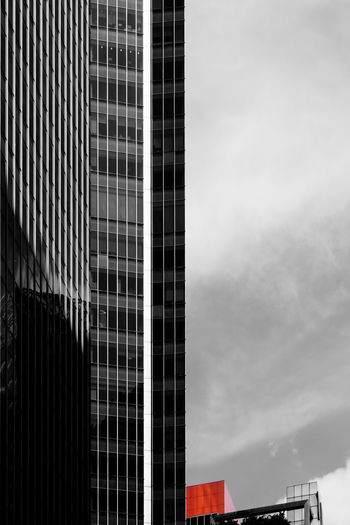 A corner of red building next to a tall modern building in black and white. Artistic BIG Cityscape Red Abstract Architecture Black And White Building Exterior Built Structure City Contrast Corner Low Angle View Modern No People Selective Color Size Sky Small Tall