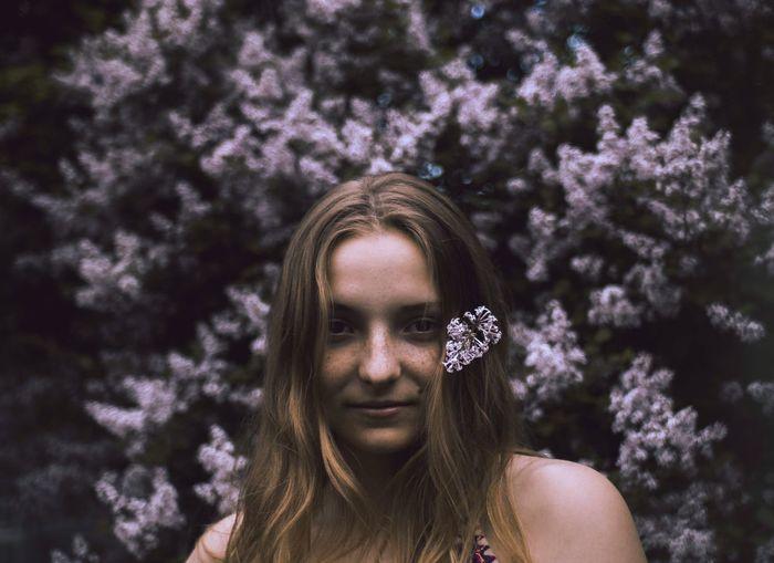 Portrait of woman against flowering plants