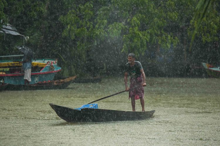 Man with umbrella on boat in river