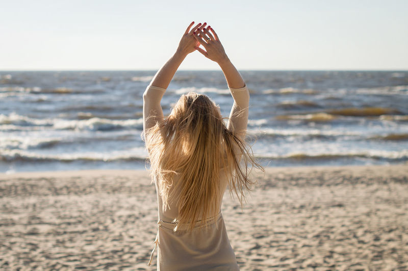 Sea Beach Land Hair Hairstyle Sky Water Women Long Hair Rear View Leisure Activity Horizon Blond Hair Nature One Person Horizon Over Water Scenics - Nature Adult Lifestyles Arms Raised Human Arm Outdoors