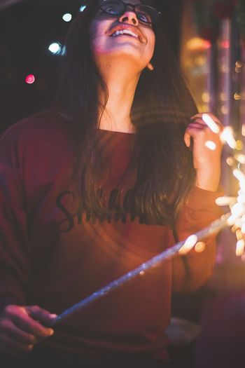 Smiling teenage girl holding sparklers while standing outdoors at night