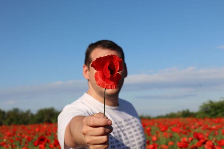 Woman holding red poppy flowers on field