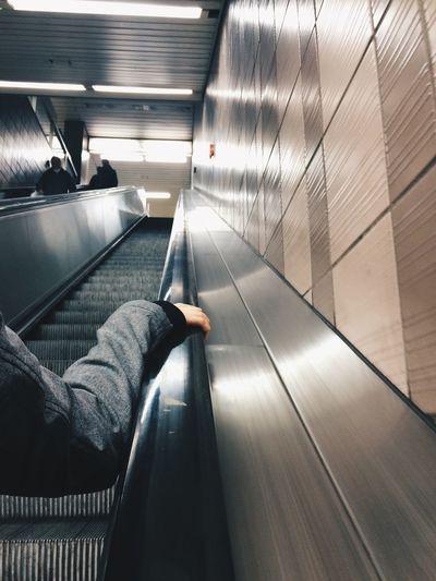 Cropped hand on escalator railing at subway station