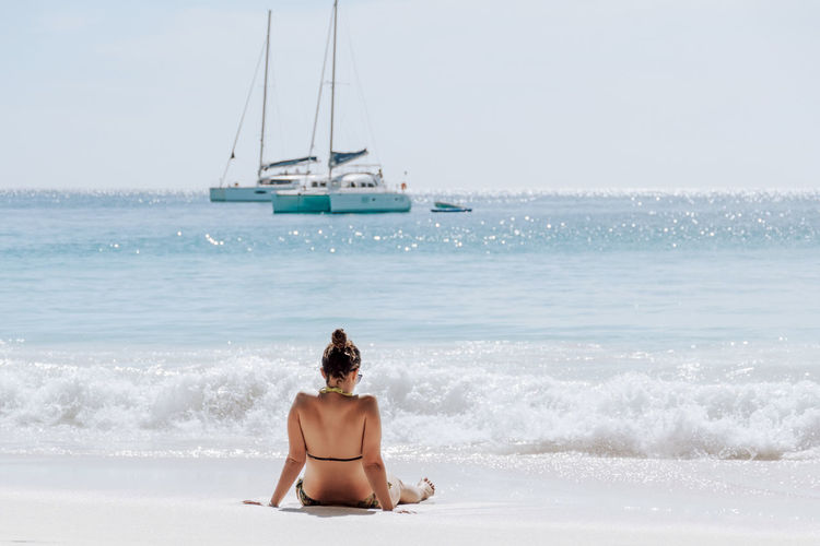 Young woman on tropical sandy beach, light and airy, waves, sailboats.