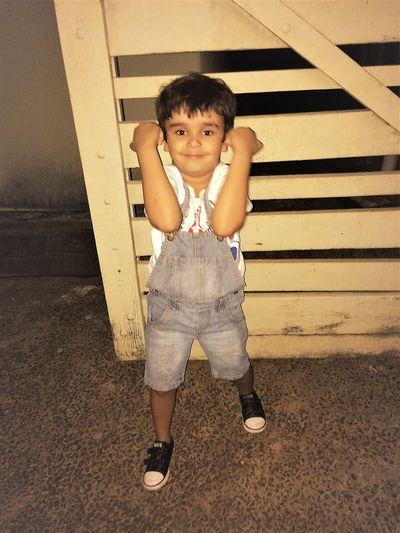 Portrait of cute boy standing against wooden door