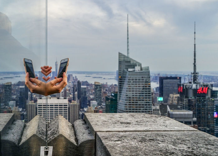 A reflection of a hand taking a picture of New York City from the Top of The Rock building. Hands Mobile Phone New York Architecture Building Exterior Built Structure City Cityscape Cloud - Sky Glass Reflection Holding Human Hand IPhone Modern Outdoors Sky Skyscraper Spire  Technology Top Of The Rock Urban Urban Skyline Wireless Technology