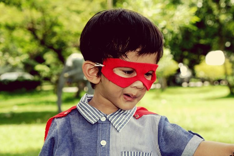 Close-Up Of Cute Boy Wearing Red Mask At Park