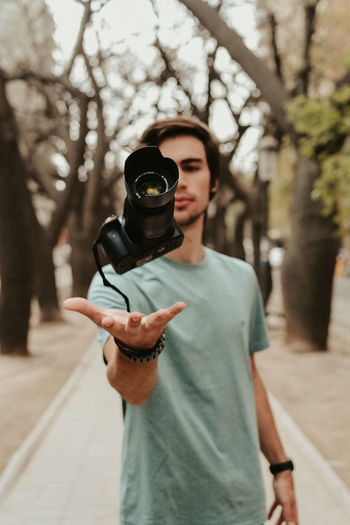 Portrait of man holding camera while standing on street