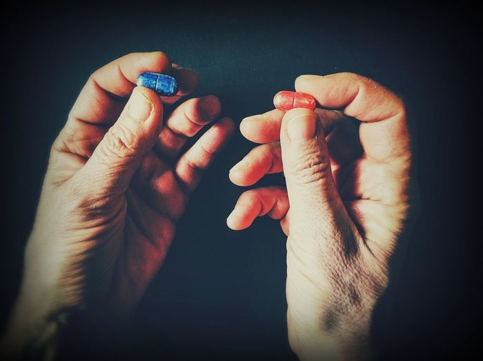 Cropped hands holding red and blue pills against black background