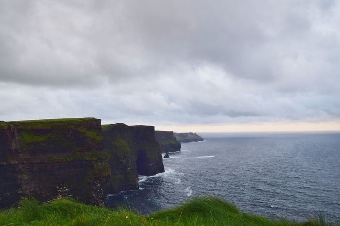 Cliffs of Moher view during cloudy sunset. Water Sea Wave Beach Cliff Sky Horizon Over Water Landscape Cloud - Sky Grass Rock Formation Coastal Feature Dramatic Sky Seascape Rocky Coastline