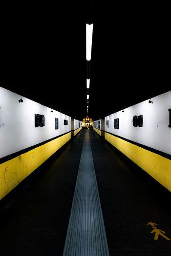 Illuminated railroad station platform at night