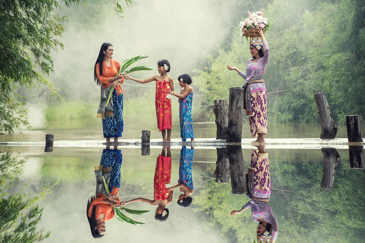 Young women with girls wearing traditional clothing standing in lake against trees