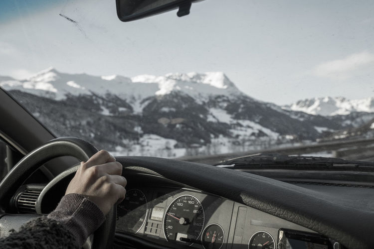 Cropped hand driving car against snowcapped mountains