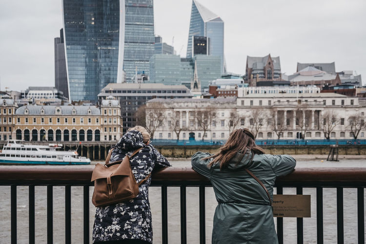 Two female tourists standing by the River Thames, London, leaning on the fence and admiring the view. Uk London Architecture Building Exterior Built Structure Real People Railing City Lifestyles Standing Sky Two People Day Water People Leisure Activity Nature Women Togetherness Three Quarter Length Casual Clothing Building Outdoors Hairstyle Office Building Exterior Skyscraper Travle Two Women Friendship Admiring The View River Thames Riverside Southbank Europe Weekend Activities Weekend Trip The Art Of Street Photography