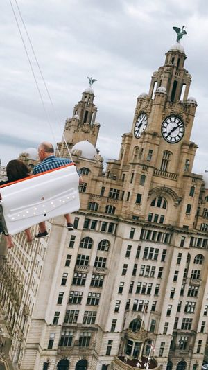 Rear view of people on amusement park ride against royal liver building