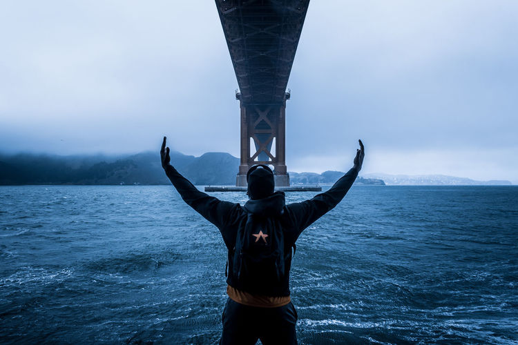 Rear view of man standing under bridge by bay against sky