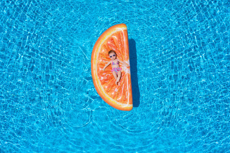High angle view of baby girl relaxing on orange shaped pool raft