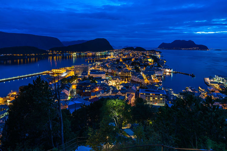 Night aerial cityscape of Alesund from Aksla hill viewpoint, More og Romsdal, Norway Norway Norwegian Scandinavia Northern Europe Norge Ålesund, Norway Alesund Art Nouveau Art Nouveau Architecture Blue Hour Cityscape Cityscape Water Sky Cloud - Sky Architecture High Angle View Built Structure Nature Sea Building Exterior Illuminated No People Scenics - Nature Beauty In Nature Mountain Plant City Nautical Vessel Tree Night Outdoors Bay