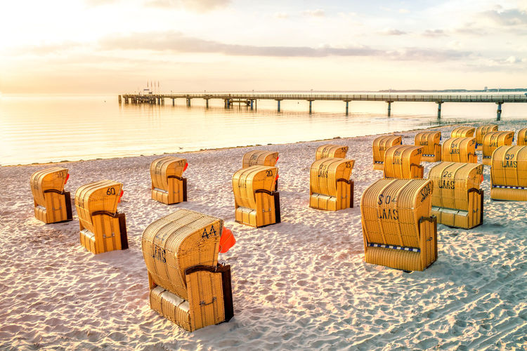 Hooded chairs on beach against sky during sunset