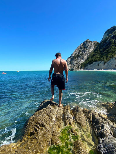 Full length of shirtless man looking at sea against clear sky