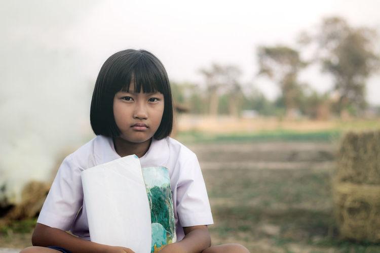 Portrait of girl sitting on field