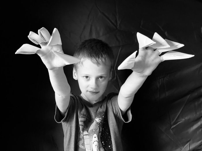 Portrait of boy holding paper while standing against black background