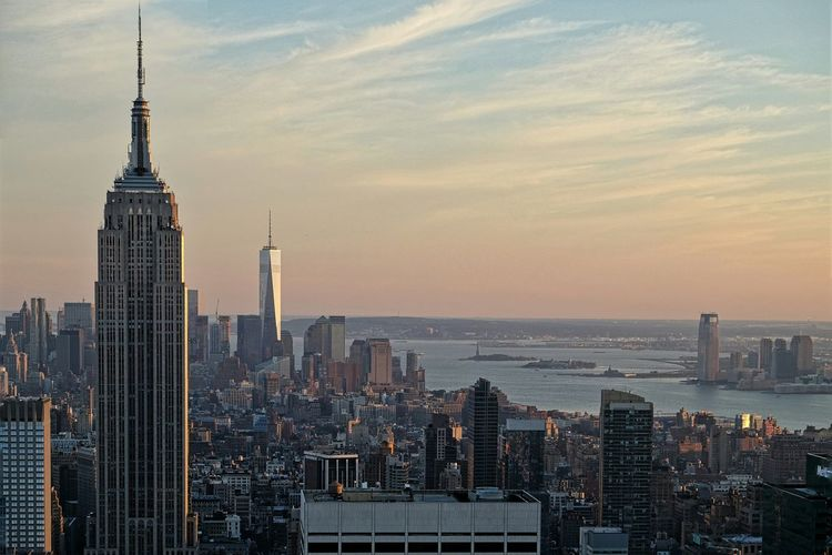 Empire state building in city against sky during sunset