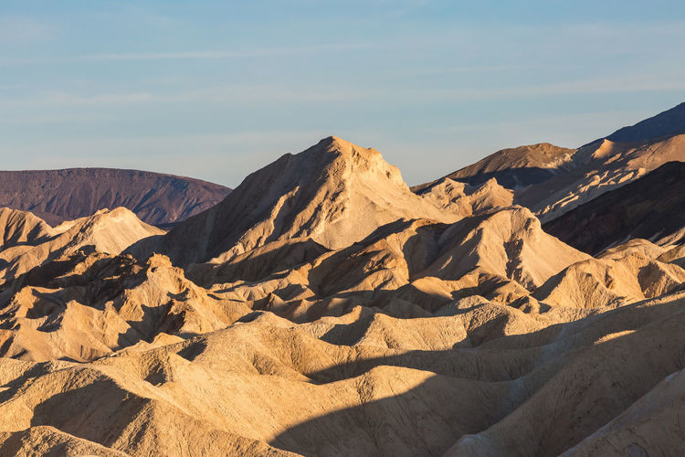 Looking out over the rocky landscape of Zabriskie Point in Death Valley, with evening light Scenics - Nature Beauty In Nature Tranquil Scene Sky Mountain Tranquility Sunlight Landscape Nature Rock Arid Climate Non-urban Scene Environment Remote Climate Physical Geography Rock Formation Land Mountain Range Idyllic No People Formation Eroded Zabriskie Point Death Valley Death Valley National Park
