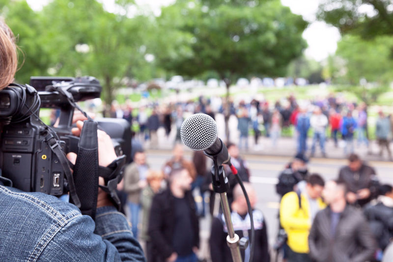 Microphone in focus, camera operator shooting blurred crowd Filming Event Meeting Politics Protest Audience Campaign Convention Crowd Demonstration Demonstrations  Election Group Mass Media Microphone People Political Presentation Protesters Rally Speaker Video Camera