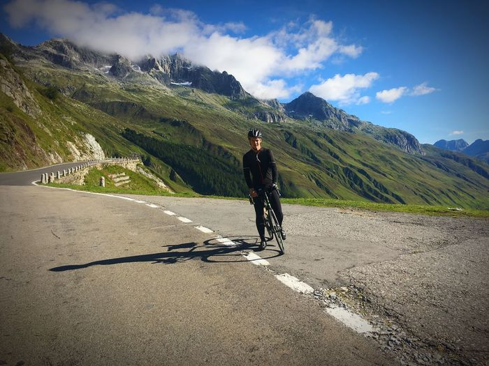 Man riding bicycle on road against mountain range during sunny day