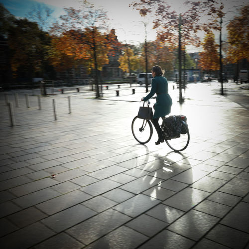 Man riding bicycle on footpath in city