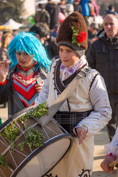 PERNIK, BULGARIA - JANUARY 26, 2018: Teen boy drummer in Bulgarian folklore costume drums loudly as part of ritual at the annual International Festival of Masquerade Games Surva in Pernik, Bulgaria KuKer Kukeri Kukeri, Bulgaria Boys Cap Celebration Childhood Clown Costume Day Elementary Age Food Girls Halloween Holiday - Event Lifestyles Outdoors People Real People Surva Togetherness Two People