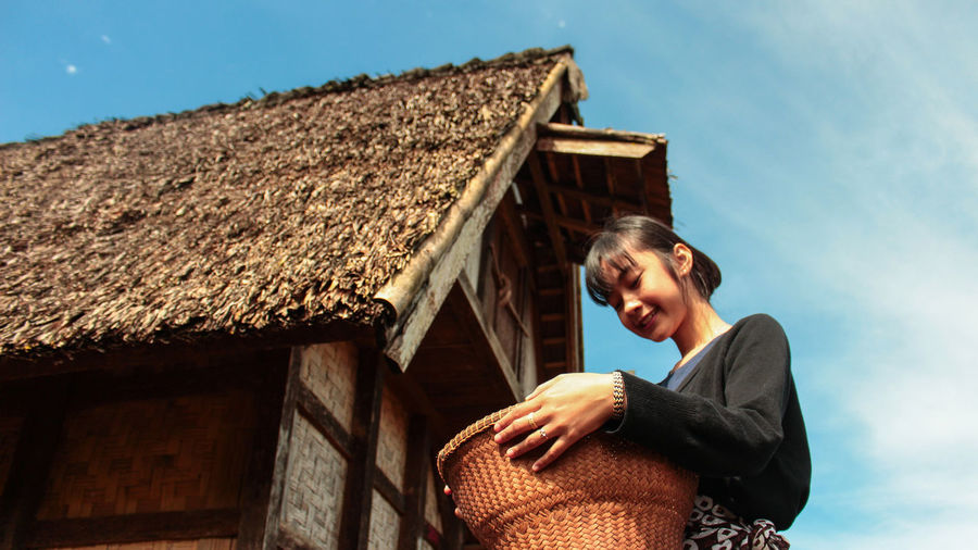 Low angle view of woman smiling and holding traditional  bucket in front of local asian hut
