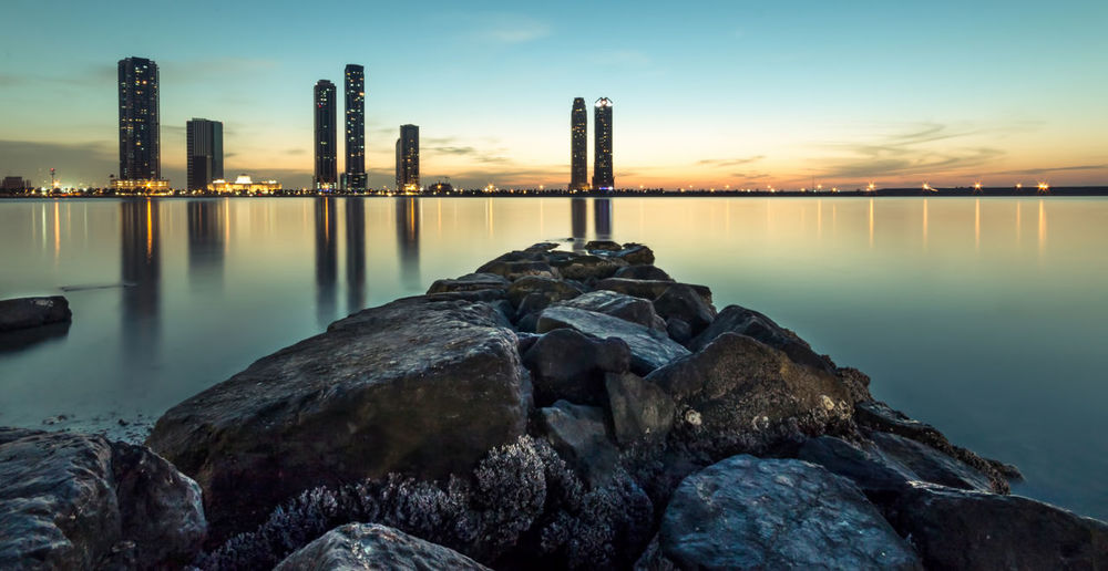 Scenic view of sea and skyscrapers against sky at sunset
