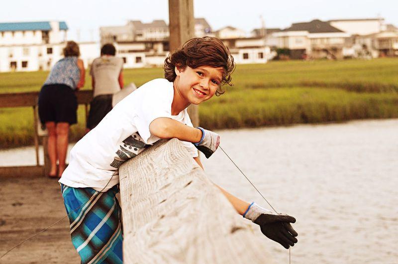 Portrait Of Boy Crabbing On Pier Over Lake