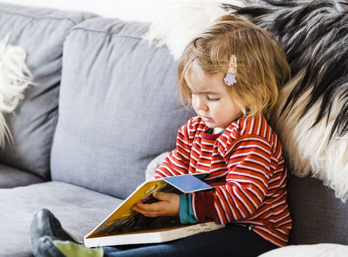 Cute Baby Girl Holding Book While Sitting On Sofa At Home