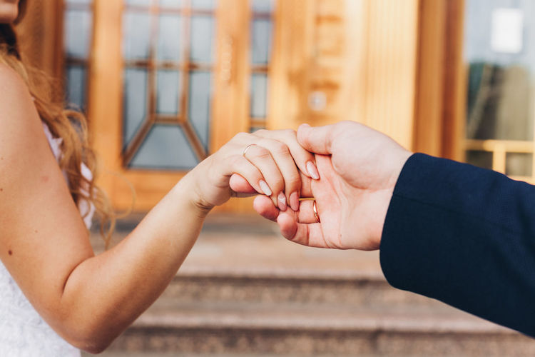 Cropped Image Of Couple Holding Hands Against Steps