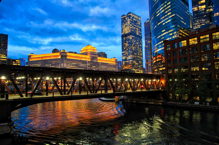 Stunning view of downtown Chicago during evening rush hour as elevated train travels across a bridge over the Chicago River with reflections of surrounding cityscape in the water. Chicago River Chicago El Downtown Chicago Elevated Track Architecture Bridge - Man Made Structure Building Exterior Built Structure City Cityscape Connection El Train Illuminated Low Angle View Modern Night Outdoors Reflection Sky Skyscraper Suspension Bridge Transportation Travel Destinations Water Waterfront
