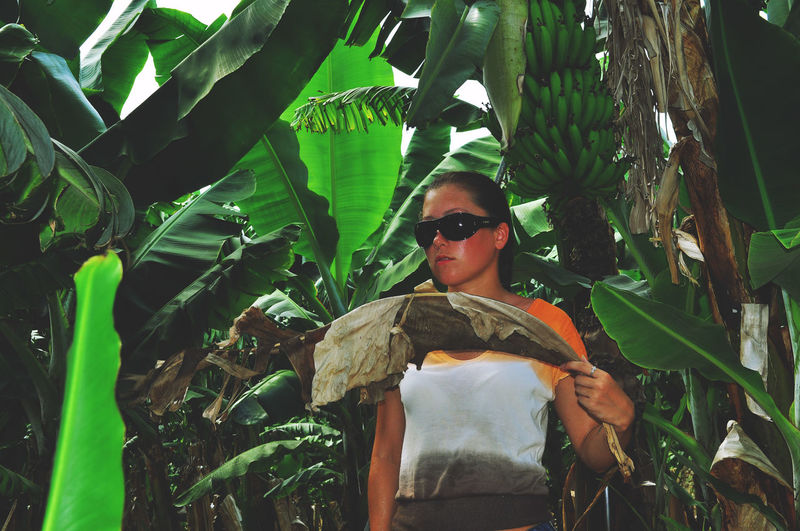 Young woman standing by banana trees