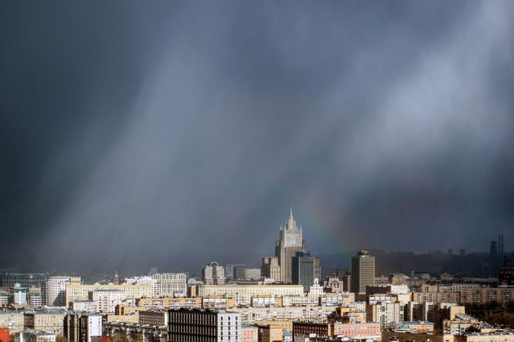 Buildings in city against rainbow and storm