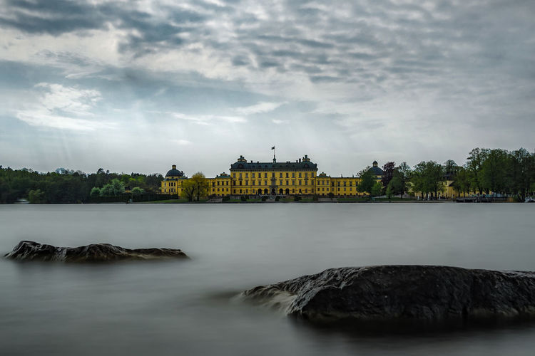 View of drottningholm palace with flowing water in foreground
