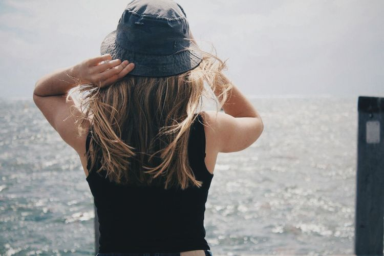 Rear view of young woman wearing sun hat standing against sea