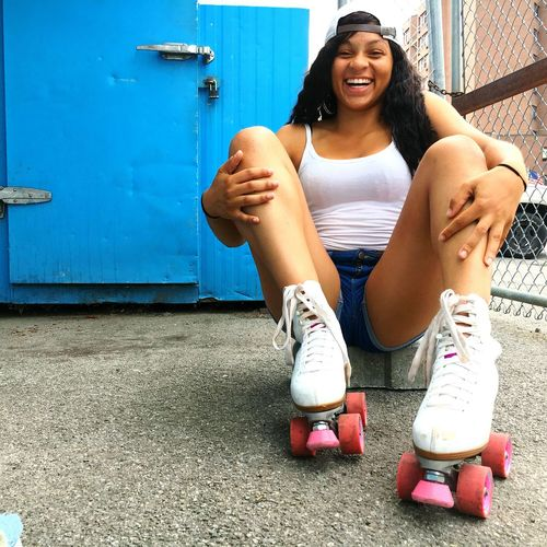 Portrait Of Young Woman With Roller Skates Sitting On Rock