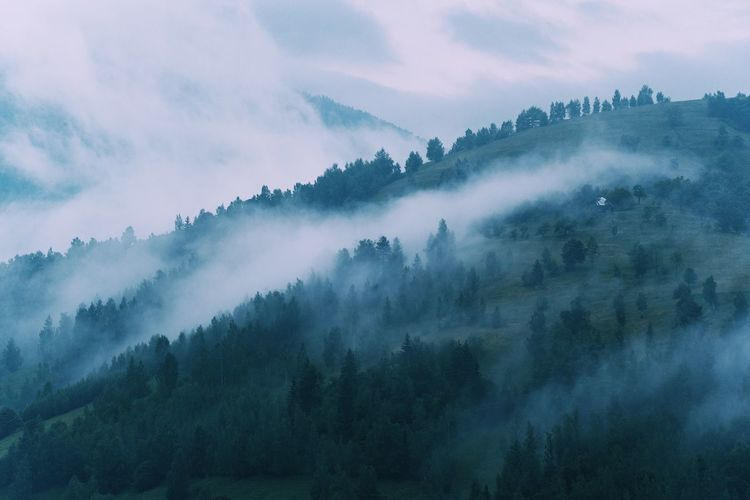Scenic view of misty mountains against cloudy sky
