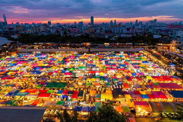 High angle view of illuminated flea market in city at dusk