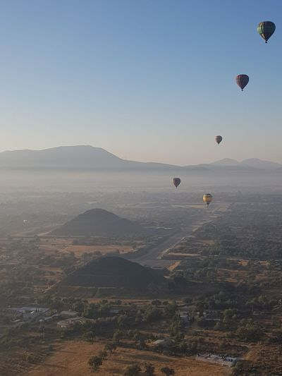 Scenic view of hot air balloons flying in sky