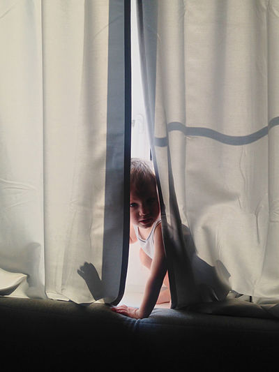 Close-up of boy hiding in curtain at home