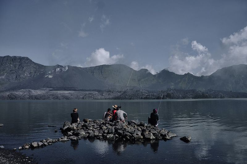 People Fishing In Lake Against Mountains
